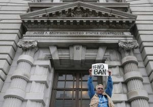 Karen Shore holds up a sign outside of the 9th U.S. Circuit Court of Appeals in San Francisco, Tuesday, Feb. 7, 2017. A panel of appeals court judges reviewing President Donald Trump's travel ban hammered away Tuesday at both the federal government's arguments and the states' challenges. (AP Photo/Jeff Chiu)