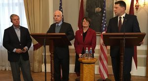 Latvian President Raimonds Vejonis, right, looks at U.S. Sen. John McCain center left, during a press conference,  Wednesday, Dec. 28, 2016, in Riga, Latvia, while Lindsey Graham, R-SC., and Amy Klobuchar, D-Minn., stand in the background. Russia can expect hard-hitting sanctions from United States lawmakers if an investigation proves that Moscow interfered in the presidential election, a U.S. senator said Wednesday during a visit to Latvia. (AP Photo/Vitnija Saldava)