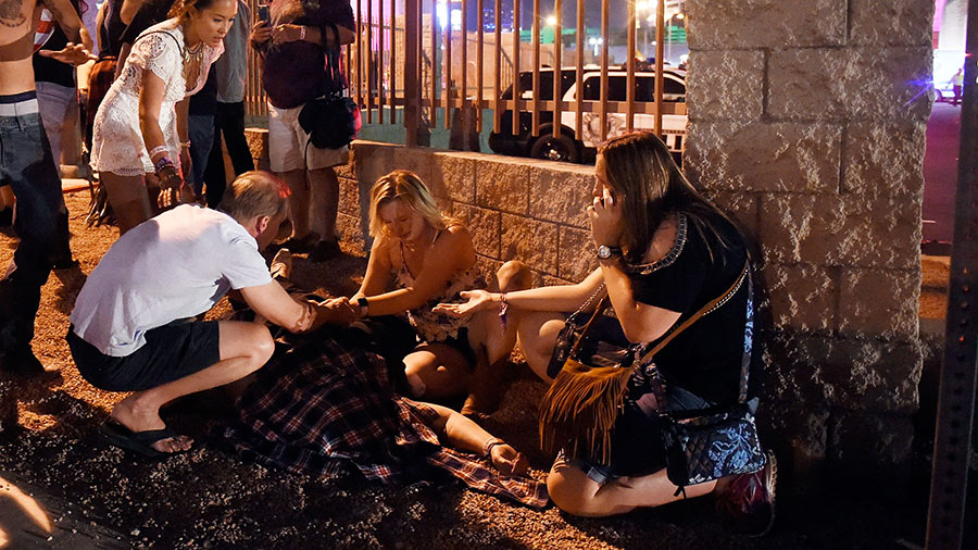 People tend to the wounded outside the Route 91 Harvest Country music festival grounds after a shooting on October 1, 2017 in Las Vegas, Nevada.