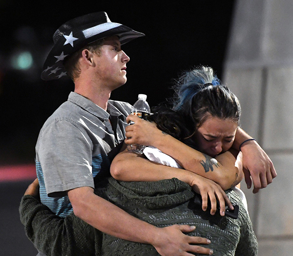 People hug and cry outside the Thomas & Mack Center after a mass shooting at the Route 91 Harvest country music festival on October 2, 2017 in Las Vegas, Nevada. A gunman, identified as Stephen Paddock, 64, of Mesquite, Nevada, opened fire from the Mandalay Bay Resort and Casino on the music festival, leaving at least 50 people dead and hundreds injured.