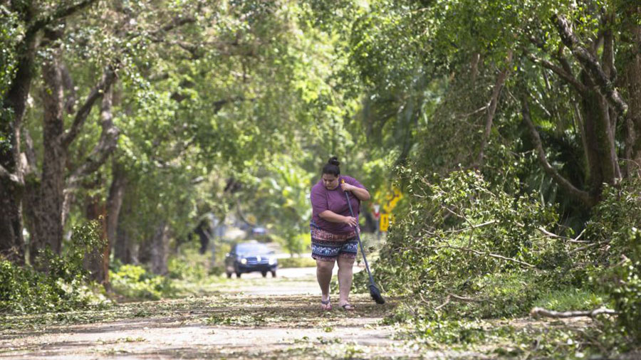A woman in Coral Gables clears the street of debris after Hurricane Irma passed through the area in Miami, Florida on September 11, 2017.