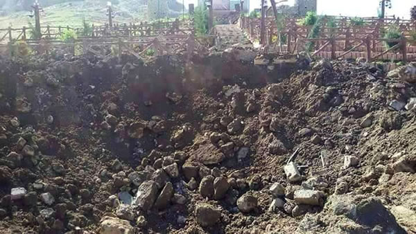 A crater is seen in the middle of a Yazidi graveyard, holding victims of ISIS and the civil war, after Tuesday's bombing by NATO member Turkey.