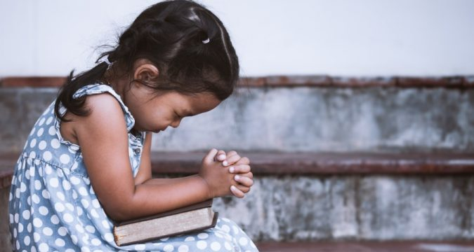 Young Girl Prays With Bible
