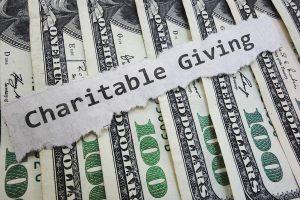 Charitable Contribution paper message on hundred dollar bills