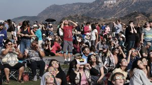 A crowd gathers in front of the Hollywood sign at the Griffith Observatory to watch the solar eclipse in Los Angeles on Monday, Aug. 21, 2017.