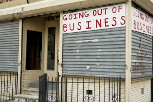 "A corner storefront with handpainted ""Going out of Business"" signs."