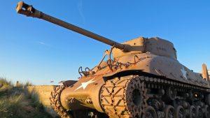 An American World War 2 tank is facing the sunset on Utah beach, Normandy.