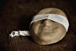 a paper-mache mask with a piece of fabric around its eyes, placed on a rustic wooden surface