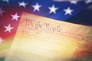 "A stock photograph of the American Constitution with the Stars and Stripes flag in the background. Focused on the words ""We the People"". Photographed at high resolution 50mp using the Canon EOS 5DSR and the 100mm f2.8 IS L macro lens. Perfect for articles or designs about politics or America."
