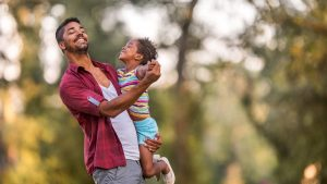 Young happy father enjoying with his small girl in the park while dancing together.