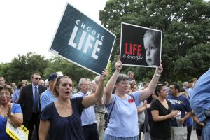 In this July 8, 2013 file photo, pro-life demonstrators express their position outside the Texas State Capitol in Austin.  Demonstrations were triggered by State Senator Wendy Davis' 11 hour filibuster to block Senate Bill 5, a measure intended to further restrict abortions.
