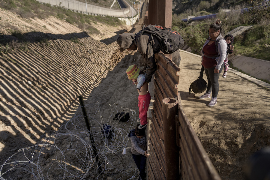 A man passes a Mexican migrant baby to her mother after they jump the border fence to get into the U.S. side to San Diego, Calif., from Tijuana, Mexico, Saturday, Dec. 29, 2018. Discouraged by the long wait to apply for asylum through official ports of entry, many migrants from recent caravans are choosing to cross the U.S. border wall and hand themselves in to border patrol agents. (AP Photo/Daniel Ochoa de Olza)