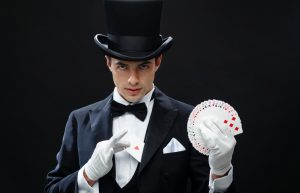 magician-showing-trick-with-playing-cards-900