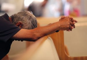 A man bows his head in prayer before the start of a service at the First United Methodist Church in Coral Springs, Fla., on Sunday, Feb. 18, 2018. The service was dedicated to the victims of Wednesday's mass shooting at nearby Marjory Stoneman Douglas High School in Parkland. Nikolas Cruz, a former student was charged with 17 counts of murder. (AP Photo/Gerald Herbert)