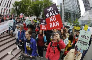 In this May 15, 2017 file photo, protesters wave signs and chant during a demonstration against President Donald Trump's revised travel ban, outside a federal courthouse in Seattle. The Supreme Court is letting the Trump administration enforce its 90-day ban on travelers from six mostly Muslim countries, overturning lower court orders that blocked it. The action Monday, June 26, 2017, is a victory for President Donald Trump in the biggest legal controversy of his young presidency.<br /> (AP Photo/Ted S. Warren, File)