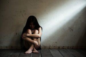 Depressed woman sitting on bare floor